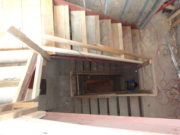 Looking down four flights of stairs in a browstone